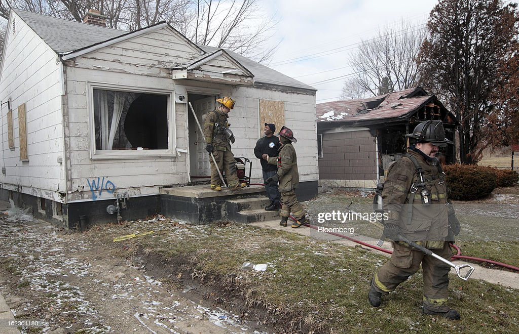 Members of the Detroit Fire Department (DFD) exit after putting out a fire in an abandoned house in Detroit, Michigan, U.S., on Thursday, Feb. 21, 2013. A fiscal emergency grips Detroit, according to a report ordered by Governor Rick Snyder, that opens a path to a state takeover of General Motors Co.'s home town, citing deficits that have stymied city officials after a $326.6 million gap last year. Photographer: Jeff Kowalsky/Bloomberg via Getty Images