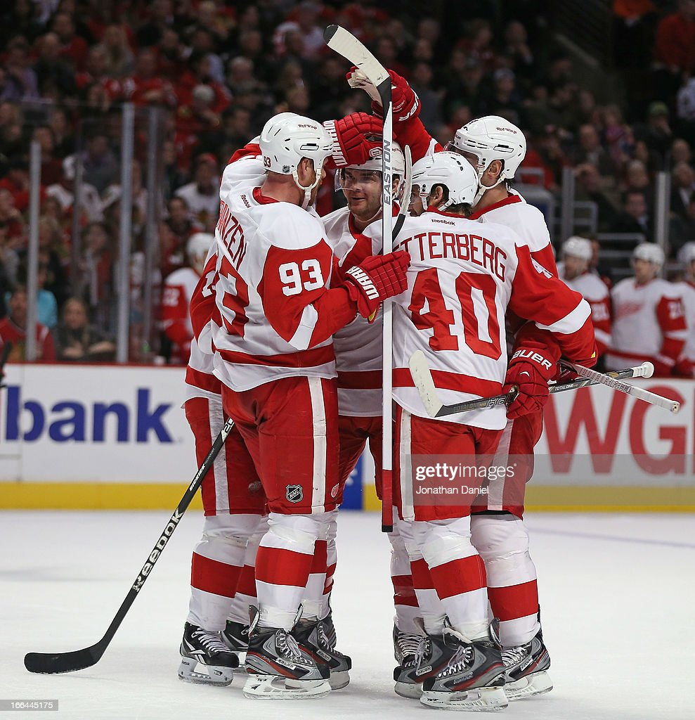 Members of the Detroit Red Wings including <a gi-track='captionPersonalityLinkClicked' href=/galleries/search?phrase=Johan+Franzen&family=editorial&specificpeople=624356 ng-click='$event.stopPropagation()'>Johan Franzen</a> #93, <a gi-track='captionPersonalityLinkClicked' href=/galleries/search?phrase=Carlo+Colaiacovo&family=editorial&specificpeople=234960 ng-click='$event.stopPropagation()'>Carlo Colaiacovo</a> #28 and <a gi-track='captionPersonalityLinkClicked' href=/galleries/search?phrase=Henrik+Zetterberg&family=editorial&specificpeople=201520 ng-click='$event.stopPropagation()'>Henrik Zetterberg</a> #40 celebrate a 2nd period goal against the Chicago Blackhawks at the United Center on April 12, 2013 in Chicago, Illinois.