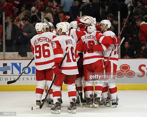 Members of the Detroit Red Wings including Tomas Holmstrom Ian White and Henrik Zetterberg celebrate a win over the Chicago Blackhawks at the United...