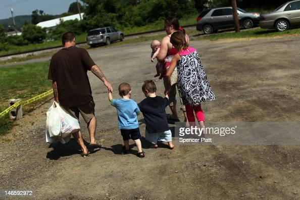 Members of the Dolan family walk home with bags of food after a food distribution by the Food Bank of the Southern Tier Mobile Food Pantry on June 20...
