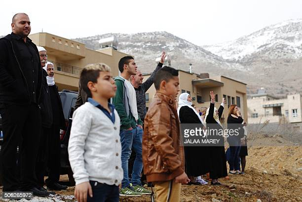 Members of the Druze community from the village of Majdal Shams in the Israelioccupied Golan Heights look towards Loay Marei a Druze man now fighting...