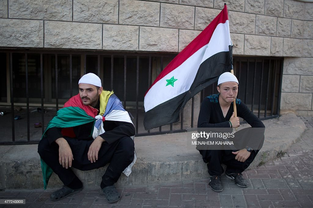 Members of the Druze community of the Israeliannexed Golan Heights sit holding the Syrian and their community's flag during a demonstration in the...