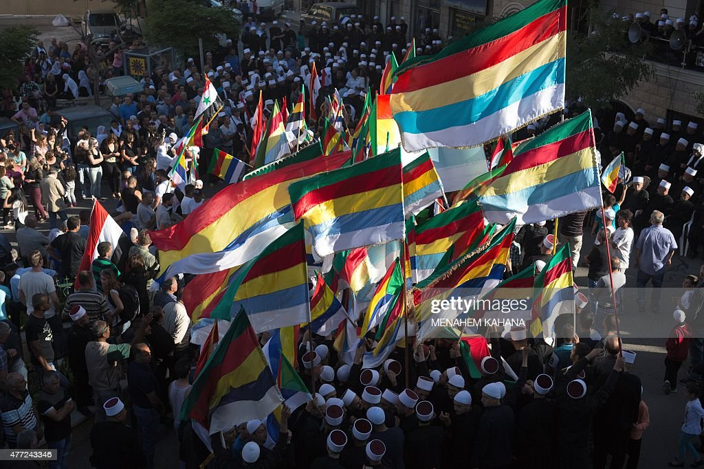 Members of the Druze community of the Israeliannexed Golan Heights wave their community's flag during a demonstration in the Druze village of Majdal...