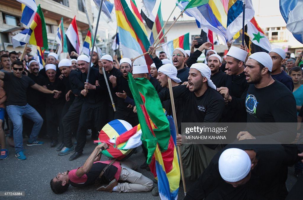 Members of the Druze community of the Israeliannexed Golan Heights wave the Syrian and their community's flag during a demonstration in the Druze...