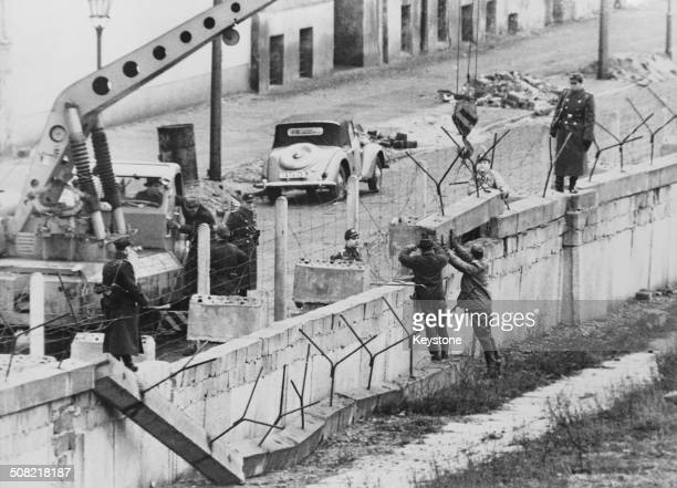 Members of the East German Volkspolizei repairing a section of the Berlin Wall after it was damaged in bad weather Boysenstrasse Berlin Germany 13th...