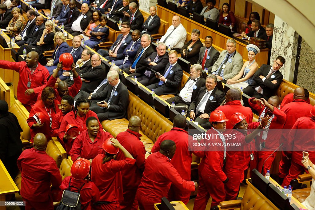 Members of the Economic Freedom Fighters political party leave the inside of parliament as during President Jacob Zuma's State of the Nation address in Cape Town on February 11, 2016. South Africa's radical leftist Economic Freedom Fighters (EFF) party walked out of President Jacob Zuma's state of the nation address after repeatedly interrupting his speech in chaotic parliamentary scenes. / AFP / POOL / Schalk van Zuydam