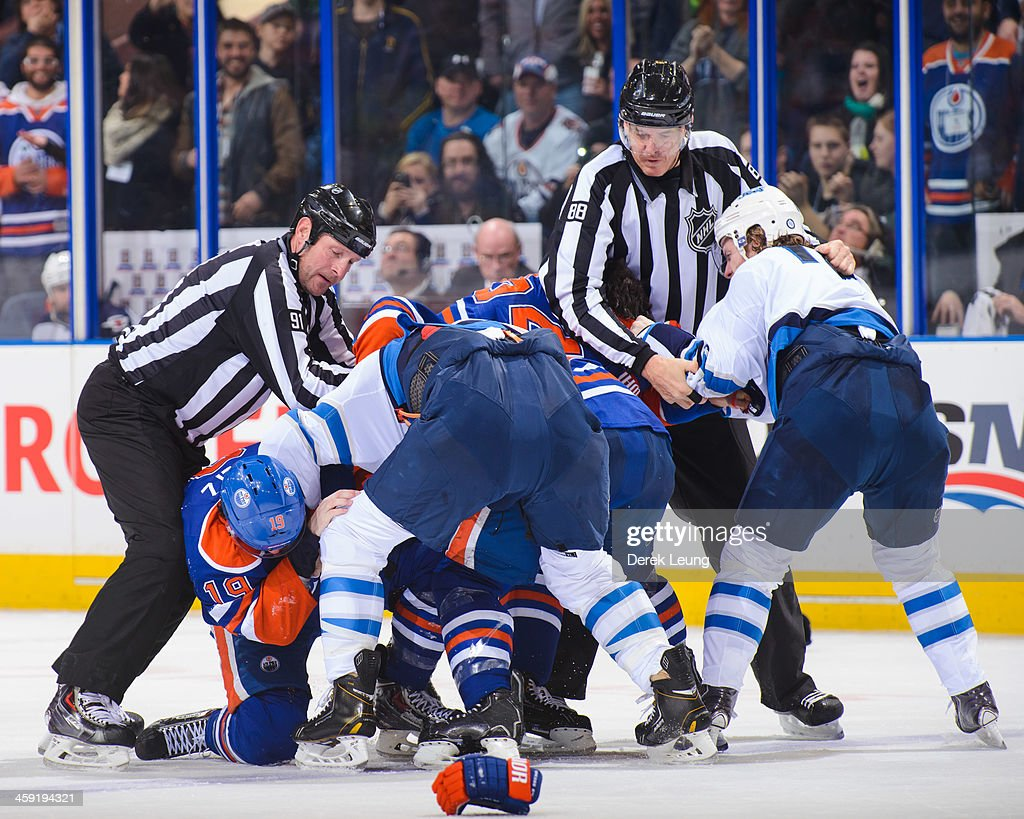 Members of the Edmonton Oilers mix it up with members of the Winnipeg Jets during an NHL game at Rexall Place on December 23, 2013 in Edmonton, Alberta, Canada. The Oilers defeated the Jets 6-2.