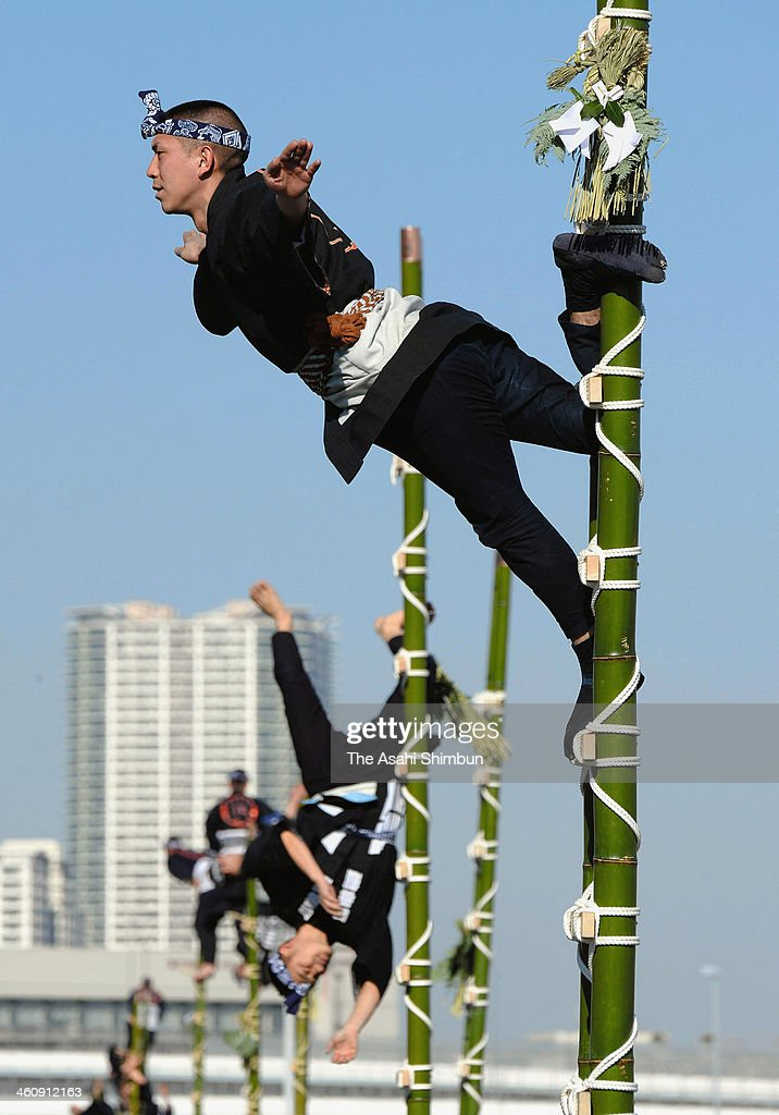 Members of the Edo Firemanship Preservation Association balance on top of bamboo ladders as they perform ladder stunts during the New Year's fire review conducted by the Tokyo Fire Department at Tokyo Big Sight on Janaury 6, 2014 in Tokyo, Japan.
