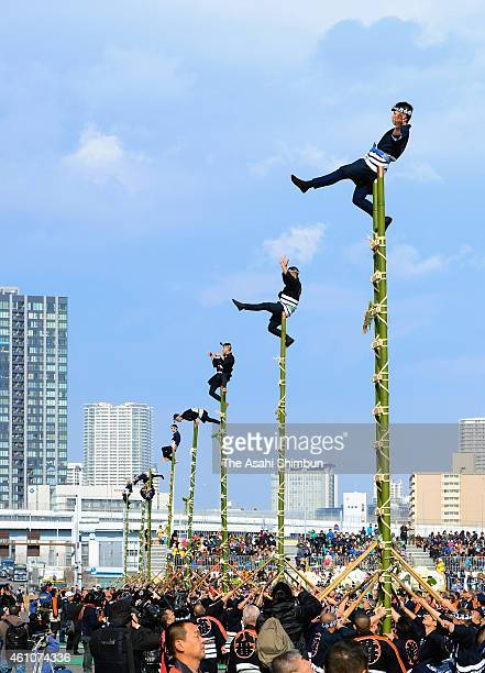 Members of the Edo Firemanship Preservation Association balance on top of bamboo ladders as they perform ladder stunts during the New Year's fire...