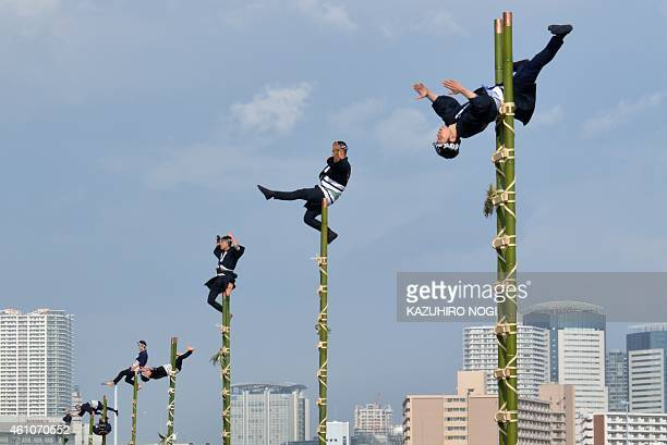 Members of the Edo Firemanship Preservation Association wearing traditional Japanese firefighting uniform perform ladder stunts during the Tokyo Fire...