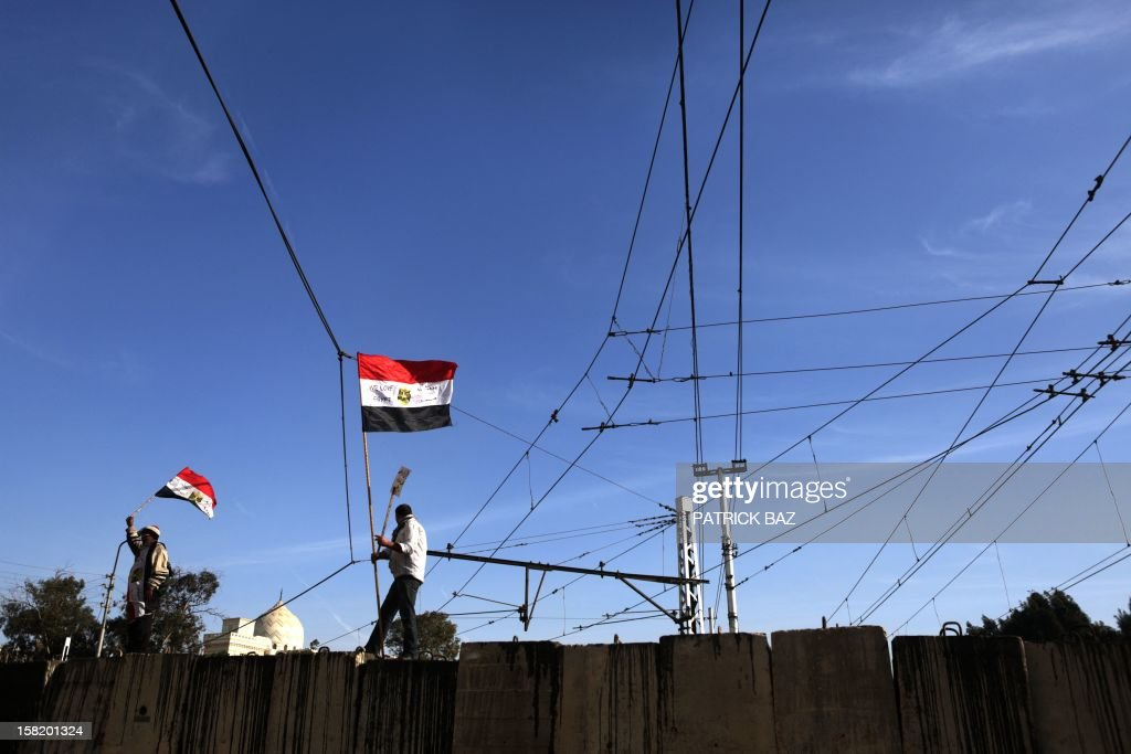 Members of the Egyptian opposition against President Mohamed Morsi wave their national flag ontop of a barricade blocking the road to the presidential palace in Cairo on December 11, 2012. Protesters started to gather in the Egyptian capital for rival rallies for and against a divisive constitutional referendum proposed by President Mohamed Morsi. AFP PHOTO/PATRICK BAZ