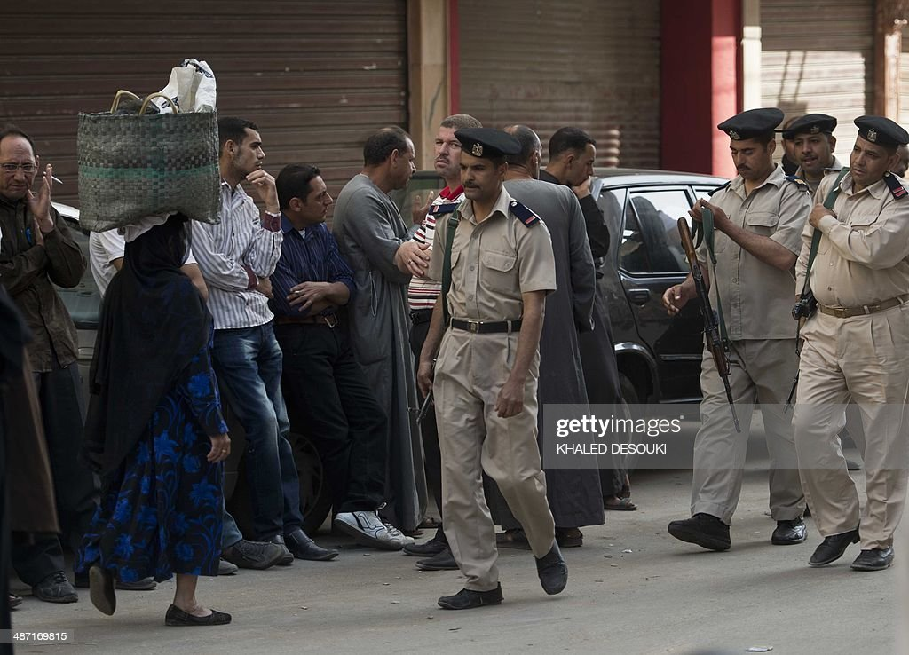 Members of the Egyptian security forces monitor the streets outside the courtroom in Egypt's southern province of Minya as relatives react after an Egyptian court sentenced Muslim Brotherhood leader Mohamed Badie and other alleged Islamists to death on April 28, 2014. The defendants were accused of involvement in the murder and attempted murder of policemen in Minya province on August 14, the day police killed hundreds of ousted Islamist president Mohamed Morsi's supporters in clashes in Cairo. AFP PHOTO / KHALED DESOUKI