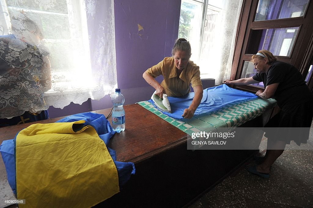Members of the election comission iron the Ukrainian flag and curtains as they prepare the pooling station for the upcoming Ukrainian presidential election at the Octyabr village in the Donetsk region on May 22, 2014. Ukrainian presidential election will be held on May 25, 2014.