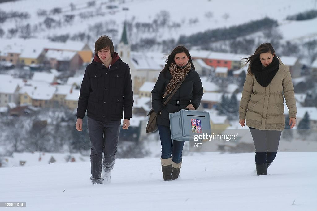 Members of the electoral commission walk through the snow with an electoral urn, to visit people living in remote, who can vote at their home on January 11, 2013 in Strani, Czech. Czech polling stations opened on January 11 afternoon in local mid-time for the first round of the first Czech direct presidential election in history. AFP PHOTO / RADEK MICA