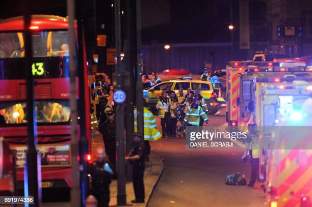 Members of the emergency services attend to persons injured in an apparent terror attack on London Bridge in central London on June 3 2017 Armed...