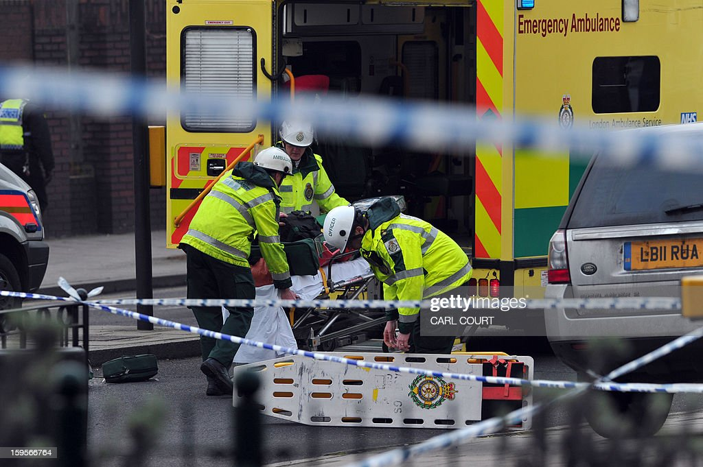 Members of the emergency services load equipment into an ambulance near the scene of a helicopter crash in central London on January 16, 2013. Two people were killed after a helicopter hit a crane at a building site and plunged to the ground in a ball of flames, police said.