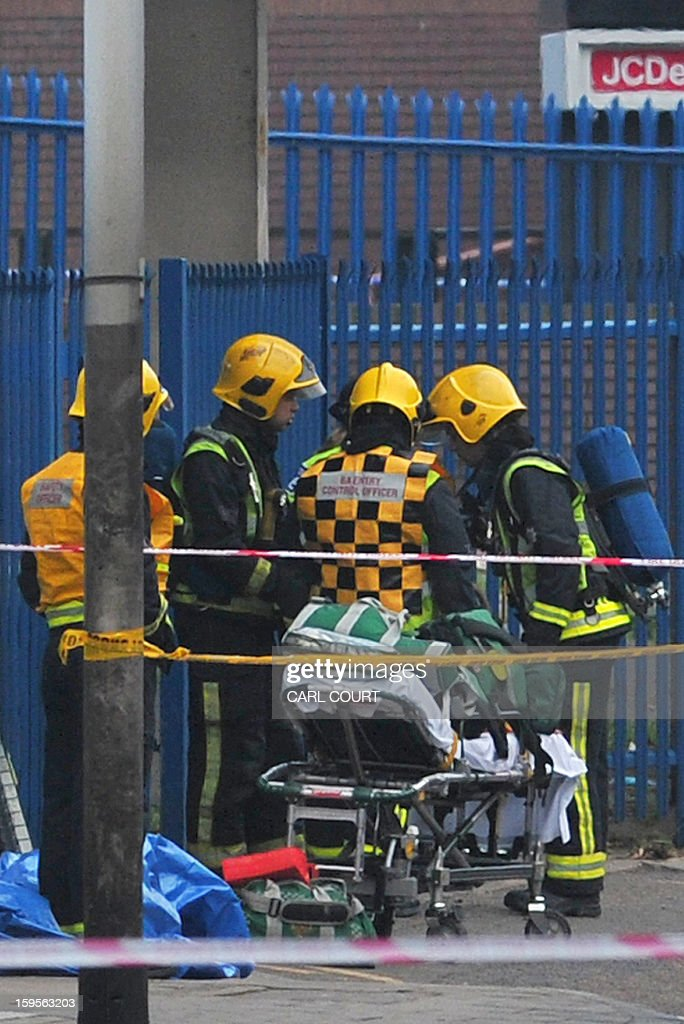 Members of the emergency services prepare a stretcher as they attend to the scene of a helicopter crash in London, on January 16, 2013. Two people were killed when a helicopter hit a crane at a building site in central London and plunged to the ground on Wednesday, police said. AFP PHOTO / CARL COURT