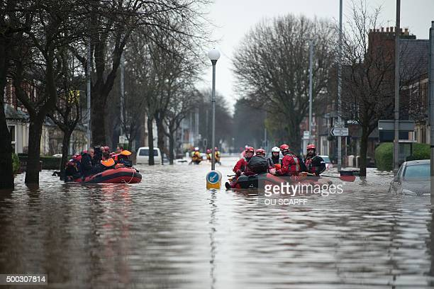 Members of the emergency services rescue residents from their flooded properties in Carlisle northern England on December 7 2015 Prime Minister David...