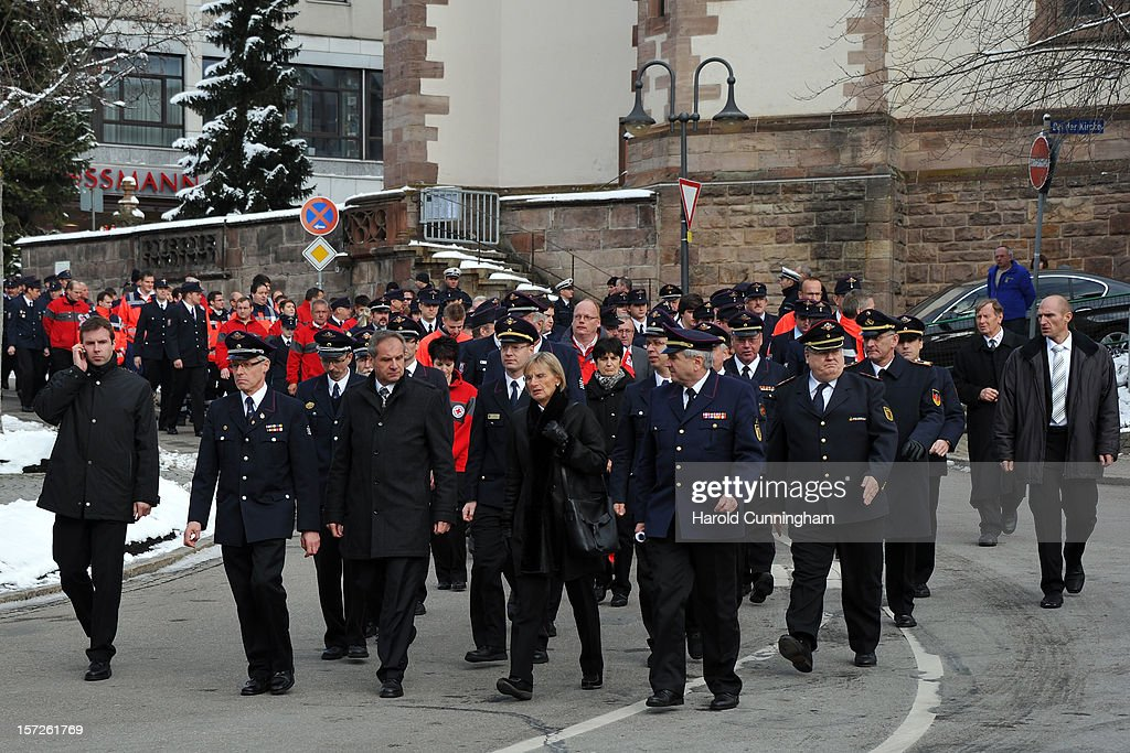 Members of the emergency services walk outside of Muenster St. Jakobus church as a memorial service is held for 14 people who died in a fire at a Caritas employment facility for the handicapped on December 1, 2012 in Titisee-Neustadt, Germany. The fire was reportedly caused by an explosion at the facility, where approximately 120 people with disabilities are employed in light manufacturing.