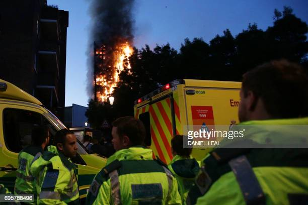 TOPSHOT Members of the emergency services watch as Grenfell Tower is engulfed by fire on June 14 2017 in west London The massive fire ripped through...