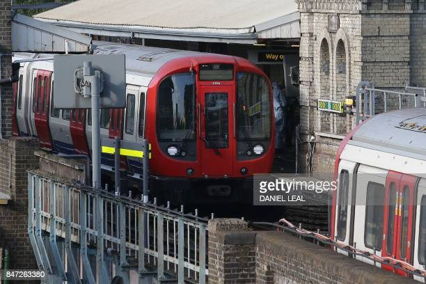 Members of the emergency services work alongside an underground tube train at a platform at Parsons Green underground tube station in west London on...