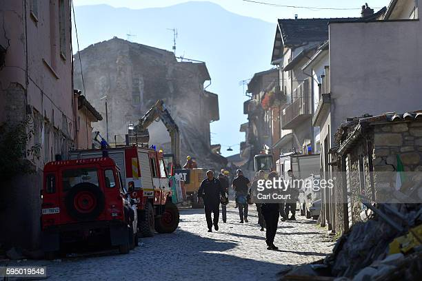 Members of the emergency services work around buildings that were damaged after being struck by an earthquake on August 25 2016 in Amatrice Italy The...