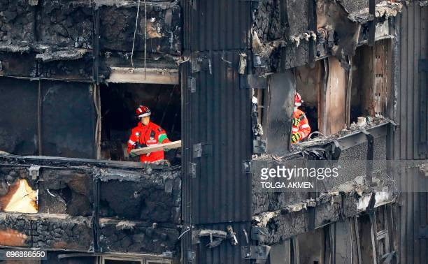 TOPSHOT Members of the emergency services work on the middle floors of the charred remnains of the Grenfell Tower block in Kensington west London on...