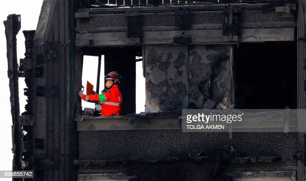 Members of the emergency services work on the top floor of the charred remnains of the Grenfell Tower block in Kensington west London on June 17...