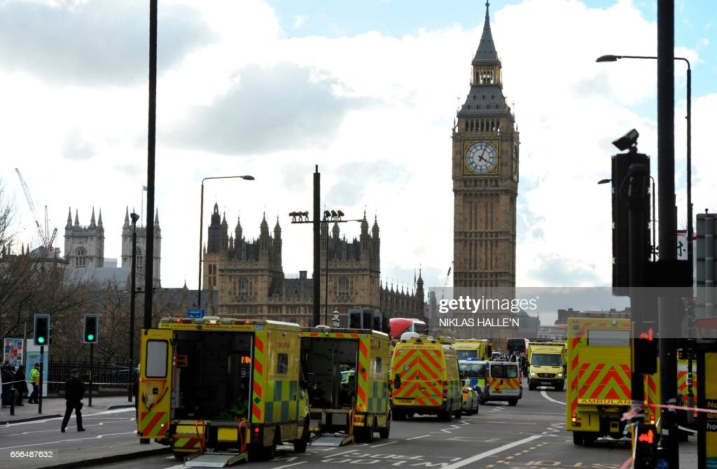 TOPSHOT - Members of the emergency services work to help vicitms on Westminster Bridge, alongside the Houses of Parliament in central London on March 22, 2017, during an emergency incident. British police shot a suspected attacker outside the Houses of Parliament in London on Wednesday after an officer was stabbed in what police said was a 'terrorist' incident. / AFP PHOTO / NIKLAS HALLE'N
