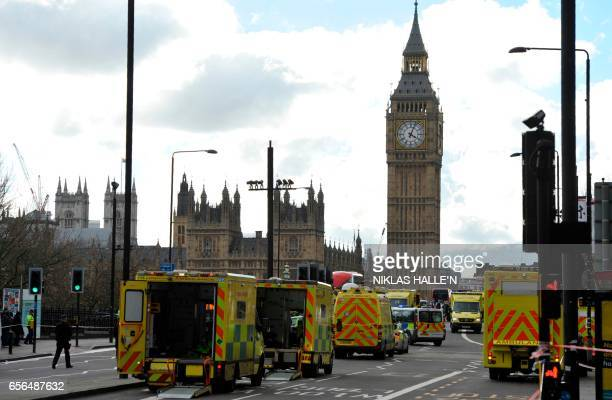 TOPSHOT Members of the emergency services work to help vicitms on Westminster Bridge alongside the Houses of Parliament in central London on March 22...