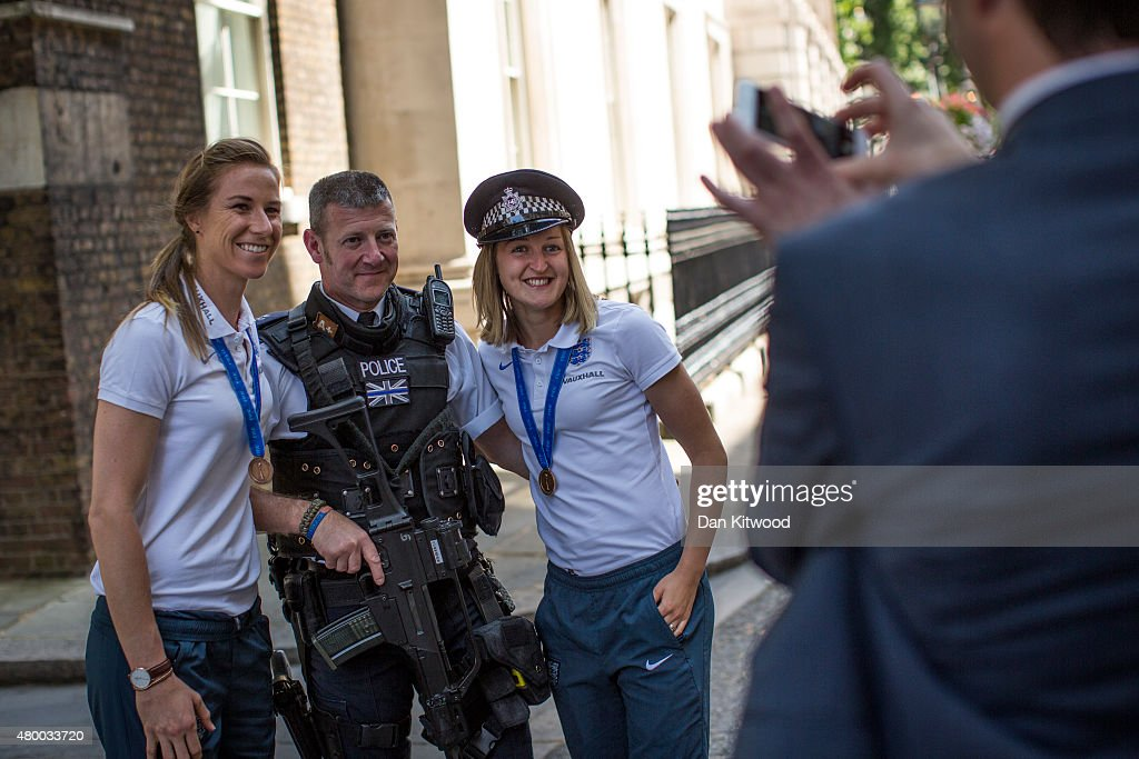 Members of the England Women's Football team Karen Bardsley and Ellen White take pose for a photo with a police officer outside 10 Downing Street on July 9, 2015 in London, England. The team met the British Prime Minister David Cameron, and earlier met HRH Prince William after returning home from their Wrold Cup campaign where they came third.