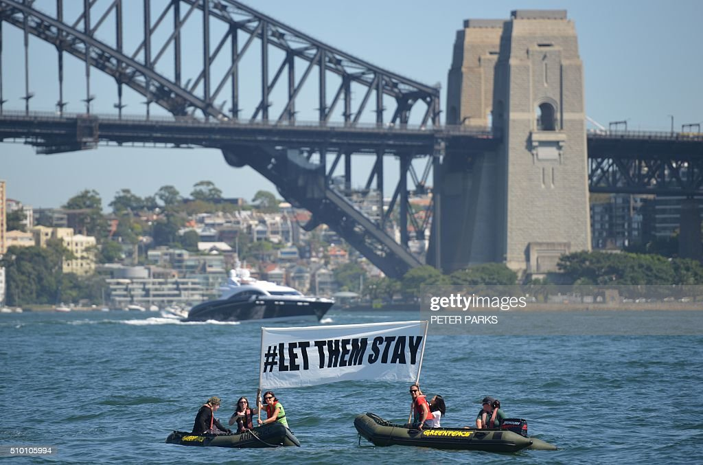 Members of the environmental group Greenpeace hold up a sign that reads '#LET THEM STAY' in front of the Harbour Bridge in Sydney on February 14, 2016. An Australian hospital in Brisbane has refused to send an asylum-seeker baby back to detention in Nauru as momentum builds across the country against offshore Pacific camps for used by the Australia government for processing refugees who try to get to Australia. AFP PHOTO / Peter PARKS / AFP / PETER PARKS
