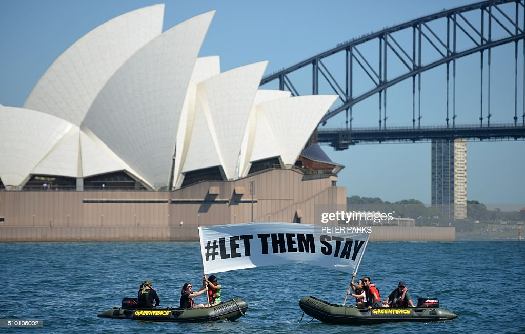 Members of the environmental group Greenpeace hold up a sign that reads '#LET THEM STAY' in front of the Opera House in Sydney on February 14, 2016. An Australian hospital in Brisbane has refused to send an asylum-seeker baby back to detention in Nauru as momentum builds across the country against offshore Pacific camps for used by the Australia government for processing refugees who try to get to Australia. AFP PHOTO / Peter PARKS / AFP / PETER PARKS