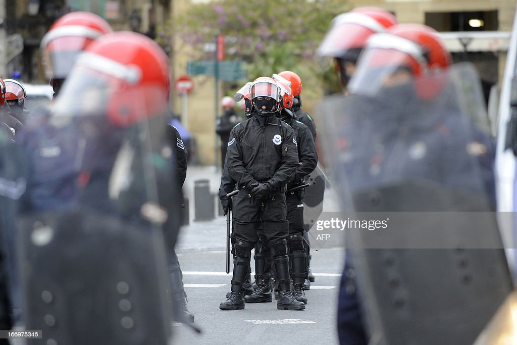 Members of the Ertzaintza Basque Police stand guard during a demonstration after six members of the Basque pro-independence youth organization SEGI were arrested in the northern Spanish Basque city of San Sebastian on April 19, 2013. Hundreds of people have remained gathered in San Sebastian during two days to try to prevent the incarceration of eight members of SEGI sentenced to six years in prison by the Supreme Court. The Spanish Court issued arrest warrants on April 16 against Mikel Arretxe, Imanol Vicente, Naikari Otaegi, Egoi Alberdi, Aitor Olaizola, Adur Fernandez, Oier Lorente y Ekaitz Ezkerra for membership in an organized armed group. AFP PHOTO / ANDER GILLENEA