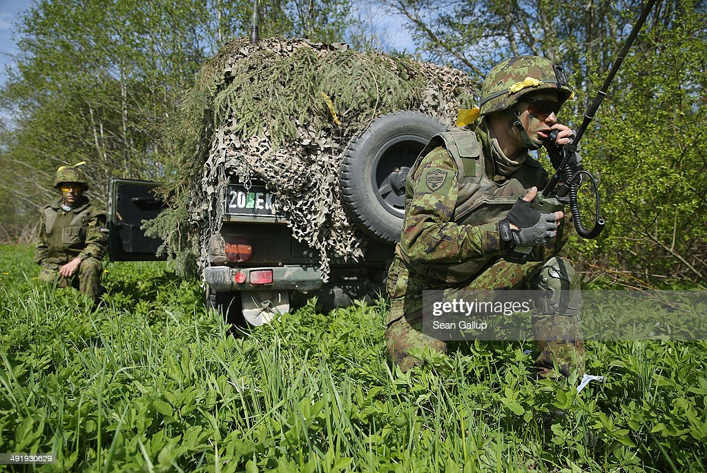 Members of the Estonian Scouts Battalion coordinate movements during the NATO 'Spring Storm' military exercises on May 18 2014 near Sengaste Estonia...