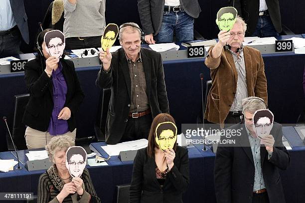 Members of the European Parliament hold up a mask depicting US intelligence leaker Edward Snowden during a voting session as part of a plenary...