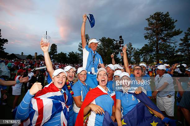 Members of the European Team hold Captain Liselotte Neumann on their shoulders as they celebrate defeating the United States 1810 in the 2013 Solheim...