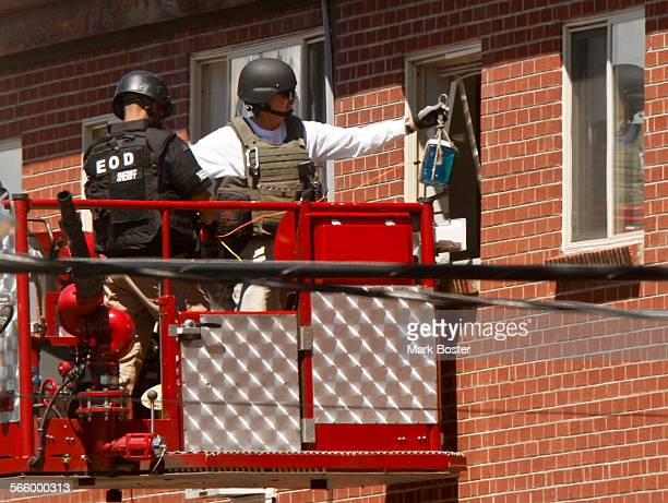Members of the Explosive Ordnance Disposal team lower an explosive device into the apartment formerly occupied by mass shooting suspect James Holmes...