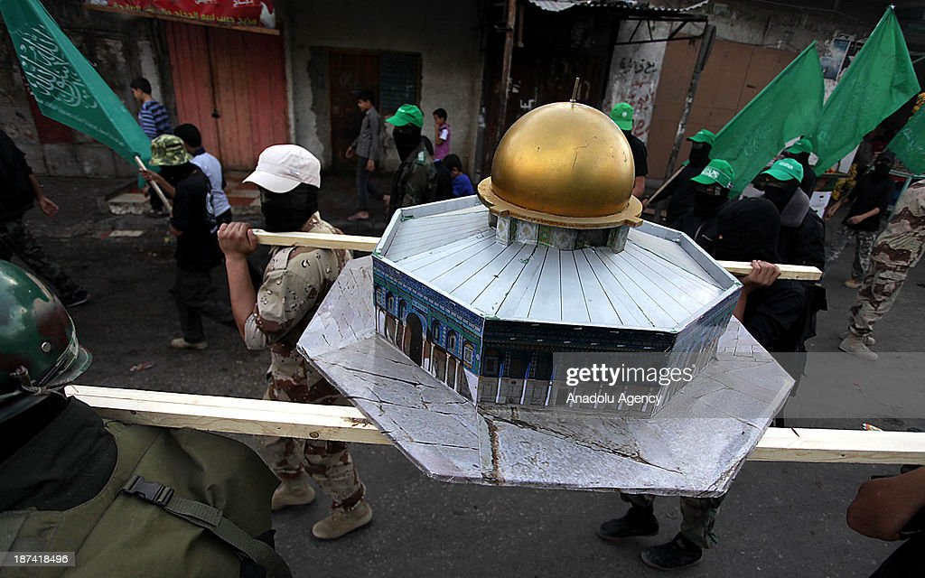 Members of the Ezzeddin al-Qassam, the military wing of Hamas, carry a model of Dome of the Rock as they march during an anti-Israel protest on the first anniversary of Israel's Operation Pillar of Defence on November 8, 2013 in the al-Nuseirat refugee camp, in central Gaza Strip. The Operation Pillar of Defence was launched in the Gaza Strip in late October 2012 after the killing of top Hamas military commander Ahmed Jaabari in an air-strike.