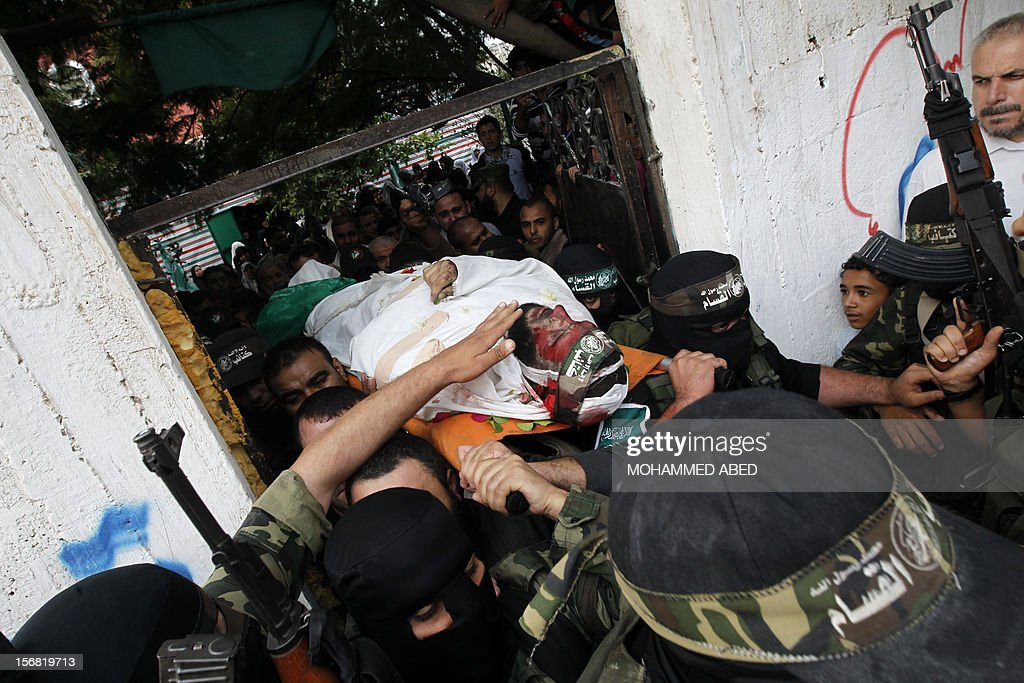 Members of the Ezzedine al-Qassam brigades, the armed wing of Hamas, carry the body of their comrade Nidal Hasan, killed the previous day, during his funeral in the Nusseirat refugee camp in the centre of the Gaza Strip, on November 22, 2012. An Egypt-brokered truce took hold in the Gaza Strip after a week of bitter fighting between militant groups and Israel, with both sides claiming victory but remaining wary.