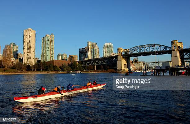Members of the False Creek Racing Canoe Club paddle False Creek from the Burrard Civic Marina with the Burrard Bridge and the Vancouver city skyline...