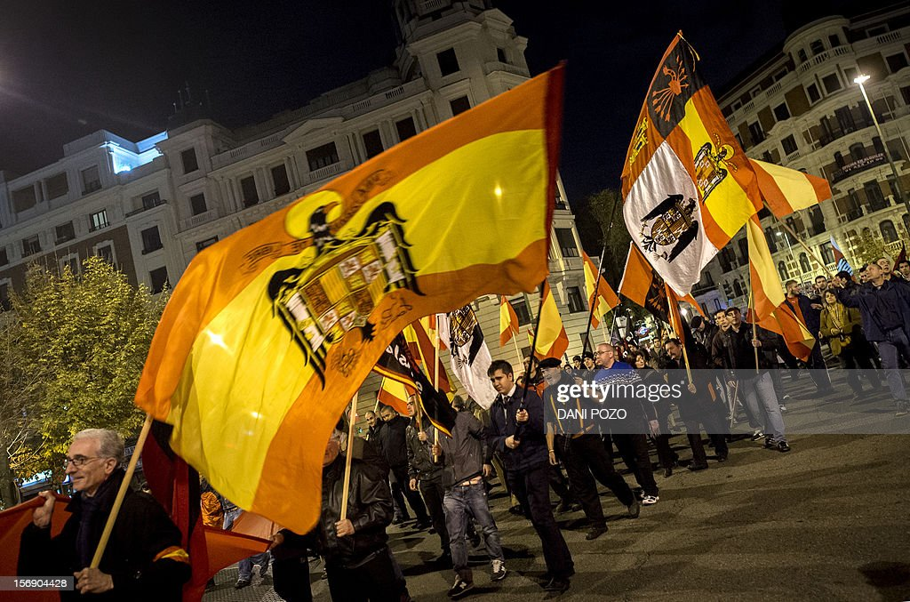 Members of the far-right Falange movement hold unconstitutional Spanish flags during a demonstration rally marking the 76th anniversary of the death of Jose Antonio Primo de Rivera, the founder of the Spanish right-wing movement, in the center of Madrid on November 24, 2012, before starting their 'Crown march' from Madrid to the Valle de los Caidos (Valley of the Fallen) where the tombs of Spain's former dictator General Francisco Franco and Primo de Rivera lie.