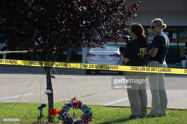 Members of the FBI Evidence Response Team gather evidence at the scene of a shooting in the parking lot of the Armed Forces Career Center/National...