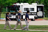 Members of the FBI Evidence Response Team investigate the crime scene outside of the Curtis Culwell Center after a shooting occurred the day before...