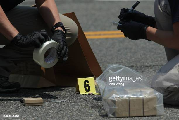 Members of the FBI Evidence Response Team mark evidence at the scene of this morning's shooting at Eugene Simpson Stadium Park June 14 2017 in...