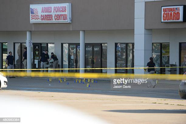 Members of the FBI Evidence Response Team work the scene of a shooting at a Armed Forces Career Center/National Guard recruitment office on July 16...