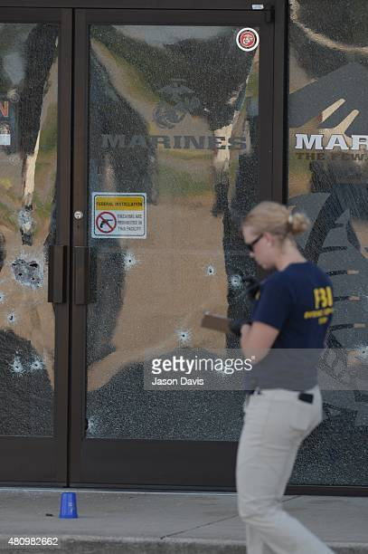 Members of the FBI Evidence Response Team work the scene of a shooting in the parking lot of the Armed Forces Career Center/National Guard...