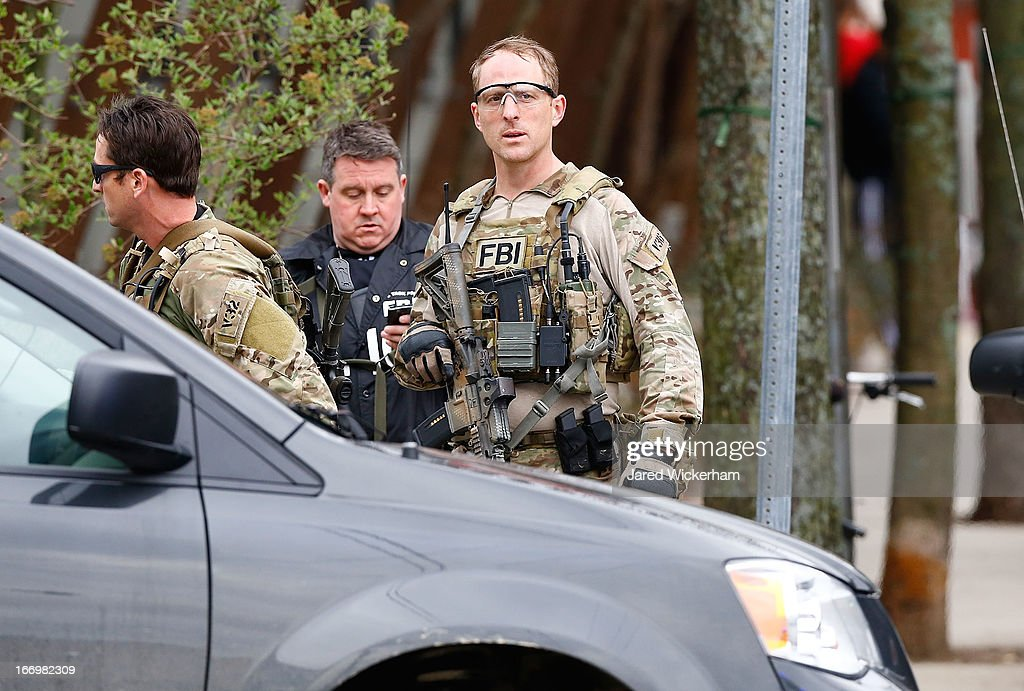 Members of the FBI, State Police, Boston Police, Cambridge Police, and other law enforcement agencies, survey the perimeter on April 19, 2013 near the home of suspect #2 on Norfolk Street in Cambridge, Massachusetts. Earlier, a Massachusetts Institute of Technology campus police officer was shot and killed late Thursday night at the school's campus in Cambridge. A short time later, police reported exchanging gunfire with alleged carjackers in Watertown, a city near Cambridge. According to reports, one suspect has been killed during a car chase and the police are seeking another - believed to be the same person (known as Suspect Two) wanted in connection with the deadly bombing at the Boston Marathon earlier this week. Police have confirmed that the dead assailant is Suspect One from the recently released marathon bombing photographs.