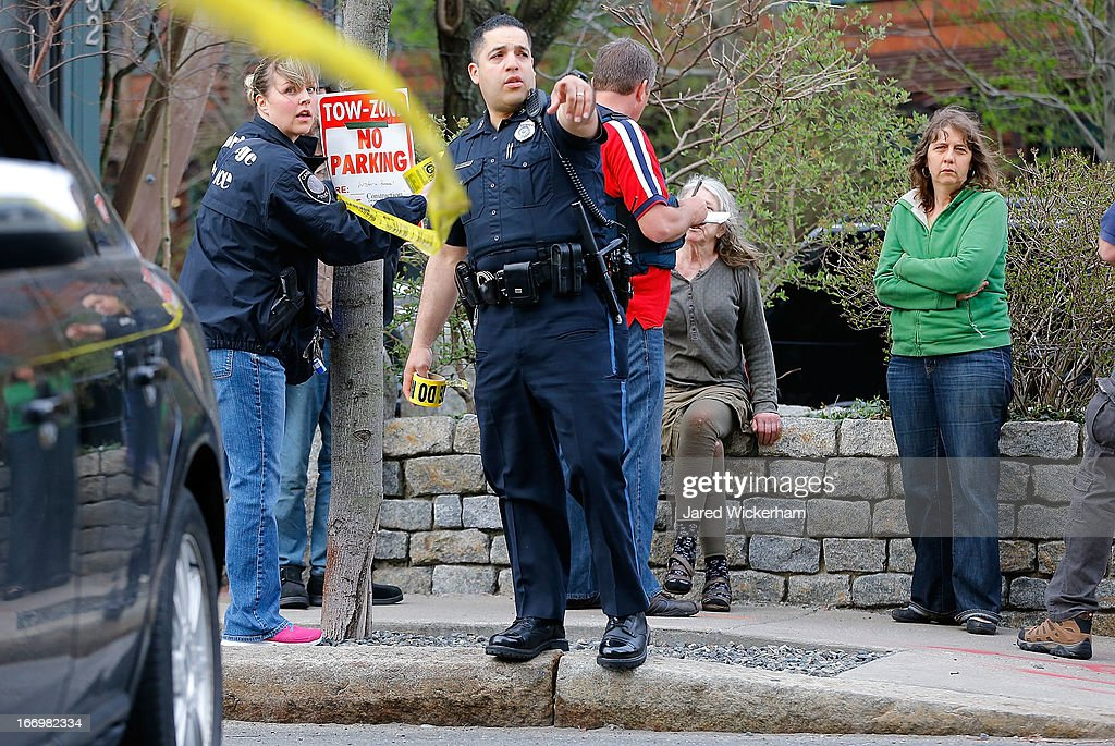 Members of the FBI, State Police, Boston Police, Cambridge Police, and other law enforcement agencies, put up police tape securing a perimeter in front of a woman being questioned by the FBI on April 19, 2013 near the home of suspect #2 on Norfolk Street in Cambridge, Massachusetts. Earlier, a Massachusetts Institute of Technology campus police officer was shot and killed late Thursday night at the school's campus in Cambridge. A short time later, police reported exchanging gunfire with alleged carjackers in Watertown, a city near Cambridge. According to reports, one suspect has been killed during a car chase and the police are seeking another - believed to be the same person (known as Suspect Two) wanted in connection with the deadly bombing at the Boston Marathon earlier this week. Police have confirmed that the dead assailant is Suspect One from the recently released marathon bombing photographs.