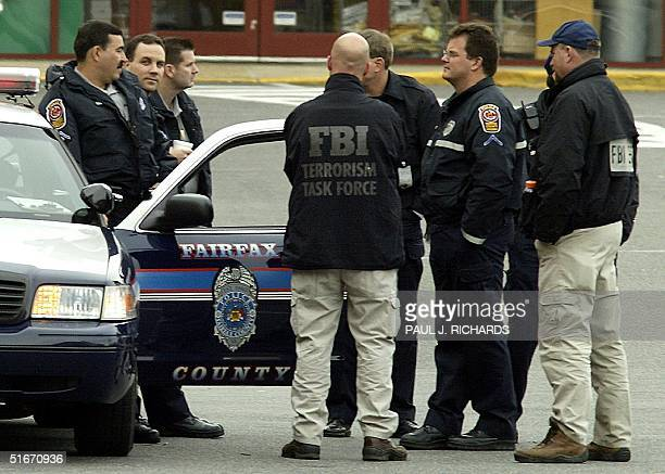 Members of the FBI talk with Fairfax police officers in the parking lot of the Home Depot construction supply store in Falls Church VA 15 October...